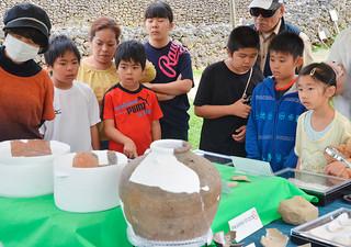 フルスト原遺跡の出土品に見入る子どもたち=20日午後、同遺跡