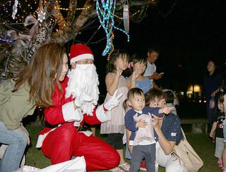 サンタクロースからプレゼントをもらった子どもたち=24日夜、市内八島町のマンタ公園