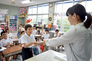 大底香奈江教諭(右)から笑顔で「のびゆく子」を受け取る児童=25日午前、平真小学校