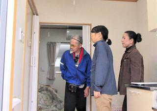 町職員に手伝ってもらい、仮設住宅に家財道具を運び込む又吉さん(左)=28日、祖納