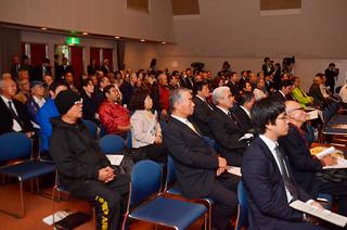 新納義馬氏の講演に聴き入る来場者ら=14日午後、市民会館中ホール
