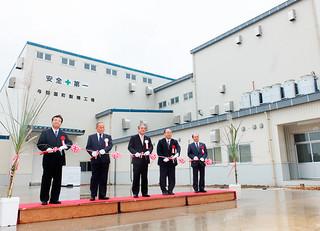 鎌で新製糖工場のテープカットを行う関係者ら=15日午後、新製糖工場