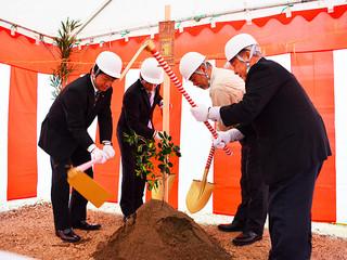 登野城小学校の新校舎増改築工事の安全を祈願してくわ入れを行う関係者ら=15日午後、同校