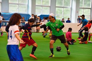 鬼ごっこで、ドリブルする子どもたちを追うサッカー女子日本代表の佐々木則夫監督(右)=17日午後、サッカーパークあかんまフットサル場