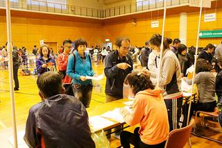会場で受付を済ませる石垣島マラソンの出場者ら=23日午後、市総合体育館サブアリーナ