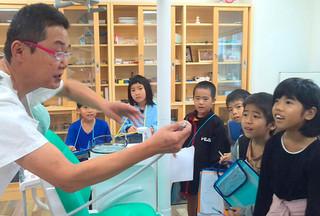 波照間歯科診療所を訪れ、歯科医の坂口克幸氏(左)から説明を受ける波照間小中学校の小学2年生たち=21日、同診療所