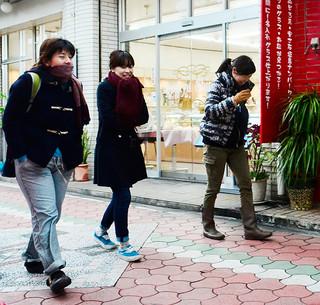 この冬一番の寒さに厚手の服を着込んで歩く人々=24日午後、石垣市美崎町