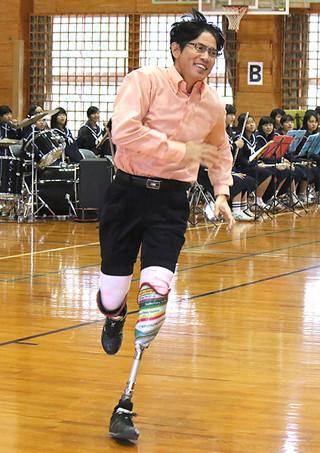 生徒の「走ってもらえますか」の要望に応え体育館を1周する島袋勉さん=25日午前、同校体育館