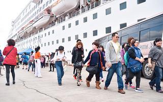 石垣島への外航クルーズ船寄港が27日からスタートする。昨年末に寄港したスーパースターアクエリアス号から下船する台湾人観光客=2015年12月30日午前