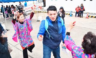 大川パナパナ会から伝統楽器「四つ竹」を渡され、踊りに加わる台湾人観光客の男性=27日午後、石垣港F岸壁