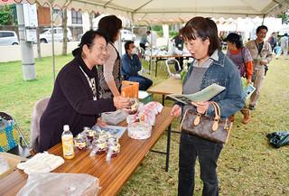 初開催の実りと食のフェスでドラゴンフルーツの加工品を販売する比嘉由子さん(左)と買い求める来場者=30日午前、伊原間公民館