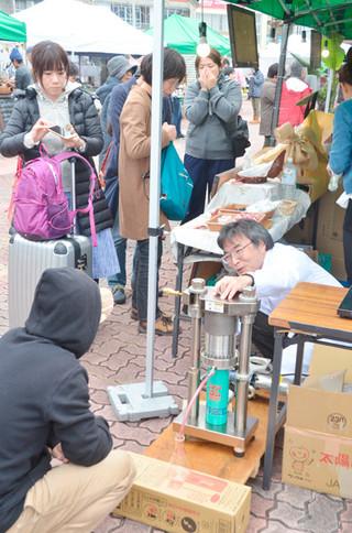 パッションフルーツオイルの抽出実演に見入るやいまさんばしマーケットの来場者ら=6日午後、旧石垣港離島桟橋