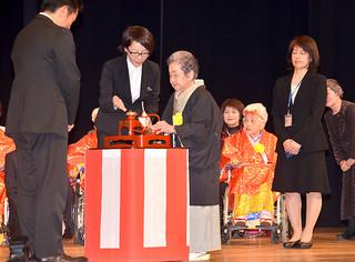 中山義隆石垣市長にあやかりの杯を授けるカジマヤーの下地ツルさん(中央)=8日午後、市民会館大ホール