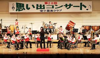 第1部でアニメメドレーなどを披露する登野城小学校器楽クラブのメンバー=27日夜、市民会館大ホール