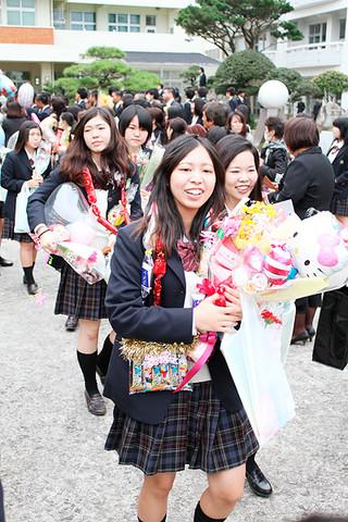 在校生や保護者らがつくる花道を笑顔で通り抜ける八重山商工高校の卒業生たち=1日午後、同校