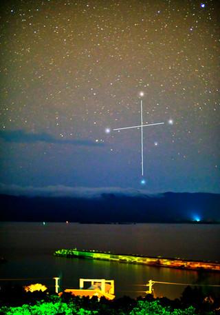 鳩間中森から撮影した南十字星。手前で横に伸びるのは鳩間島の桟橋。奥に見える島影は西表島=8日午前2時ごろ(川口ひろしさん提供)