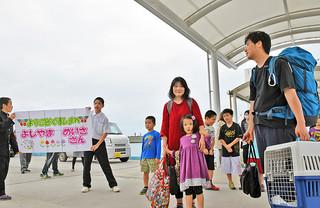 黒島に降り立った吉山医師一家と、歓迎に駆け付けた黒島校の児童生徒ら=18日午後、黒島港。