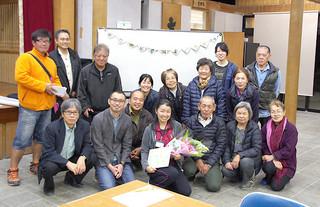 竹富島の住民から花束を贈られた町保健師の坂内由紀さん=24日、竹富島まちなみ館