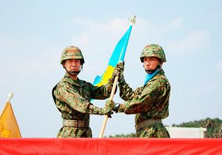 小川清史西部方面総監から隊旗を受け取る塩満大吾監視隊長(右)=28日午前、与那国駐屯地内