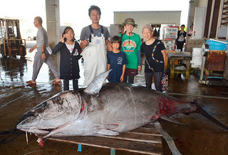 今季初の水揚げとなった413.8㌔の本マグロと釣り上げた田中船長(中央)=30日午前、八重山漁協