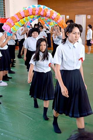 笑顔でアーチをくぐり、入場する八重山農林高校の新入生たち=7日午後、同校体育館