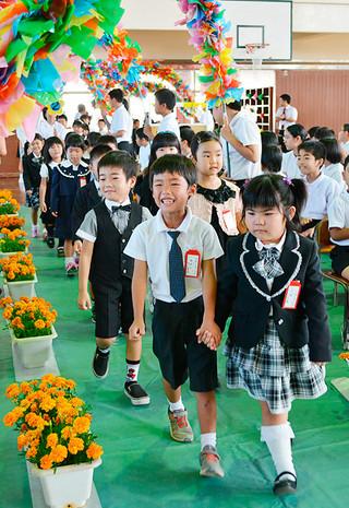 手をつなぎ、笑顔でアーチをくぐり抜けて入場する登野城小学校の新1年生たち=8日午前、同校体育館