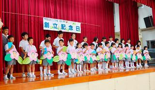 海星小学校の新入生歓迎会でパートナーの6年生からもらった似顔絵と絵本を手にうれしそうな表情の1年生たち=11日午前、同校体育館