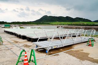 船越漁港の構内に運ばれ、設置を待つ浮桟橋=13日午後、同漁港