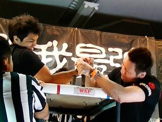 プロ無差別の決勝戦で識名徹夫を攻める金城晃(右)=17日午後、大川公民館