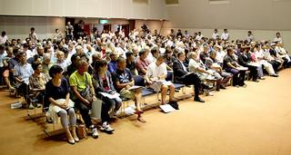 防衛省が主催した自衛隊配備計画の説明会に参加する人たち=22日夜、市民会館中ホール