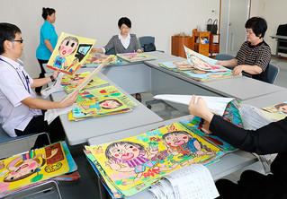 小学校低学年の部の作品から入賞作品を選ぶ審査員ら=26日午後、本社会議室