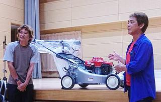 三盛光祐館長に芝刈り機を寄贈する西里行広さん(右)=27日夜、上原公民館(同公民館提供)