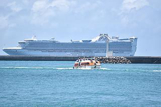 石垣に寄港した外航クルーズ船で最大の「ゴールデンプリンセス」(奥)と上陸する乗客を乗せたテンダーボート(手前)=7日午後、南ぬ浜町から撮影