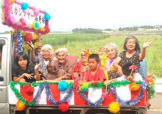 妹やひ孫とともにトラックの荷台に乗り、カジマヤーパレードを行う石野梅さん(中央)=4日午前、波照間島