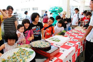 ゴーヤを使った創作料理の試食コーナー。子どもたちも味見をしていた=8日午前、JAファーマーズマーケットやえやまゆらてぃく市場