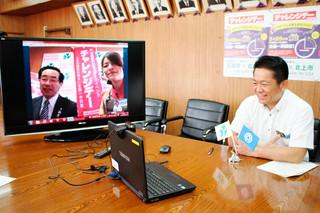 北上市の髙橋敏彦市長(テレビ画面左)とエールを交換する中山義隆市長=9日午前、庁議室
