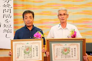 功労者表彰で表彰された仲大盛吉幸部会長(右)と東恩納武氏=20日午後、JAおきなわ宜野湾支店ジュビランス