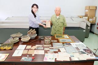 戦時中の紙幣など164点を寄贈した平田一雄さん(右)と八重山平和祈念館の宮良晴美さん=20日午前、同祈念館