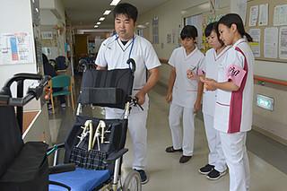 かりゆし病院のふれあい看護体験で、車いすや歩行補助器具などの説明を受ける我謝任千圭さん(右から2人目)ら=21日午前、同病院
