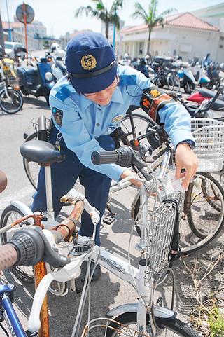 無施錠の自転車に「ツーロック」を呼び掛けるひも付きのカードをくくりつける警察官=3日午前、石垣港離島ターミナル駐輪場