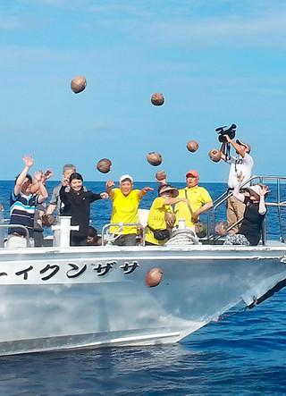 「愛のココナッツメッセージやしの実流し」で91個のやしの実を海に流す参加者=8日、石垣島沖合(石垣市観光交流協会提供)