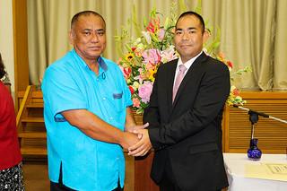 沖縄県議会議員選挙で当選し、固い握手を交わす砂川利勝氏(左)と次呂久成崇氏=9日午前、県庁講堂