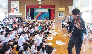 場内を移動しながらビオラを演奏、児童らと交流する奏者=7日、与那国小学校体育館