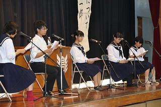八重氏の詩を朗読する放送委員の生徒ら=21日午前、同校体育館