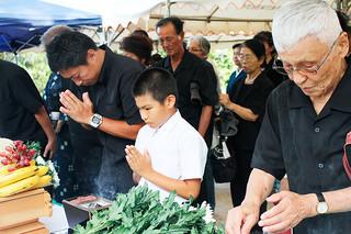 石垣市主催の全戦没者追悼式・平和祈念式の参列者。式後、焼香を行い、戦没者の冥福を祈る=23日夕、八重守乃塔