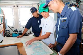 山城満船長(右)から海図の説明を受ける金城悠太朗君(中央)=28日午後、巡視艇あだん船内