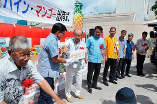 石垣島産パイン・マンゴーゆうパックを配達車両に積み込む関係者ら=28日午前、八重山郵便局