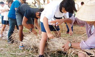 古代舟作りを手伝う久部良中の生徒ら=24日、ナーマ浜公園