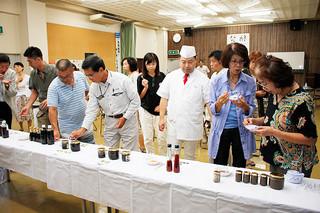 黒麹を使って開発された発酵調味料の試作品を試食する人たち=4日午後、石垣市商工会館ホール