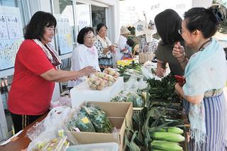 野菜など多彩な品物が並ぶおっかあ市で接客する伊野田集落の女性ら(左)=3日午前、伊野田集落センター
